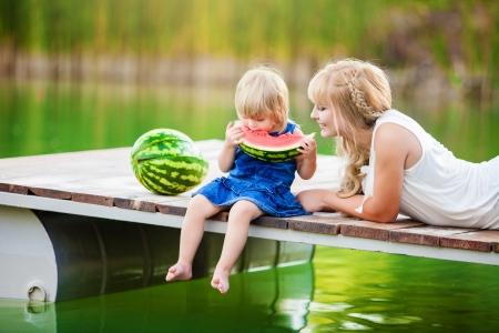 frutas divertidas: joven familia feliz de picnic en el parque verde con lago