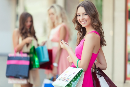 or spree: Shopping woman holding bags with a group of friends at the background Stock Photo