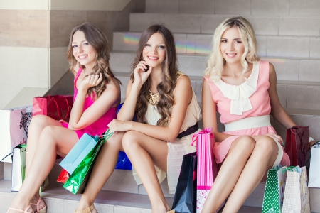 Three beautiful girlfriends with Shopping Bags in mall on the stairs photo