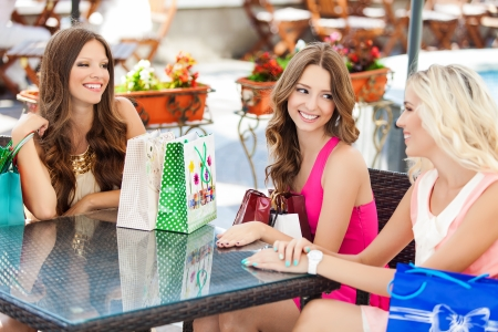 having a break: beautiful young women friends in cafe on a terrace after the shopping