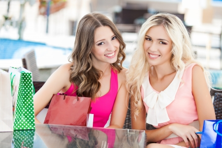 Two beautiful young women friends in cafe on a terrace after the shopping Imagens