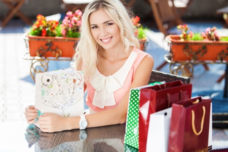 Young beautiful woman with shopping bags in a cafe on the street Stock Photo