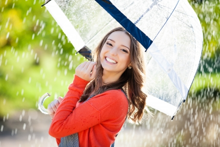 Beautiful young woman holding umbrella out in the rain Stock Photo