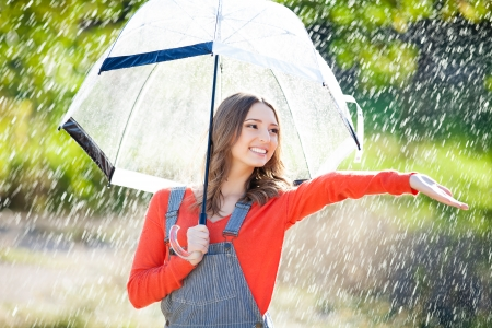 Beautiful young woman holding umbrella out in the rain photo