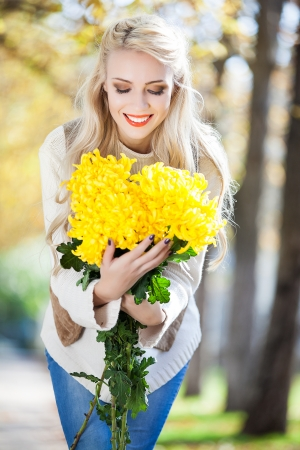 Young woman with bouquet of yellow flowers in hand in beautiful autumn park, concept autumn photo