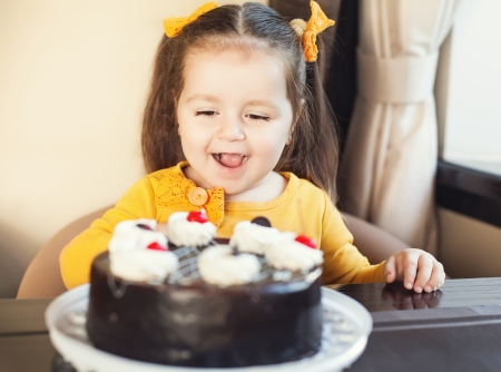 happy little girl indoors with a birthday cake photo