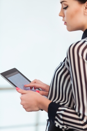 females: Young smiling business woman holding digital tablet computer
