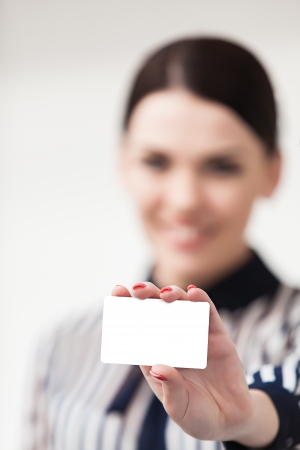 Smiling businesswoman showing and handing a blank business card photo