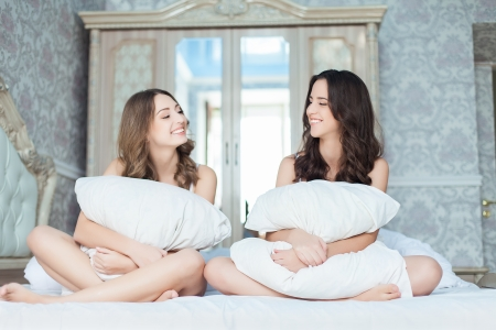 Two Beautiful Women with pillow laughing together on the bed photo