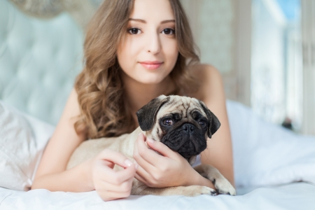 Attractive young girl with dog while laying on a bed photo
