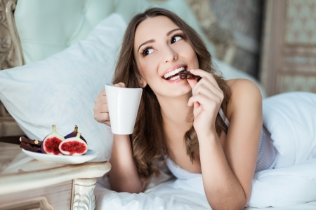 Attractive woman with a cup on the bed Imagens