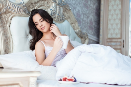 Attractive woman with a cup on the bed Stock Photo - 23235518