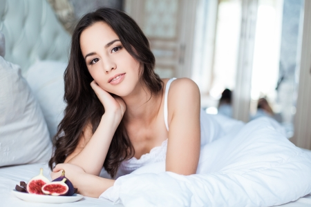 Attractive woman with a figs on the bed Stock Photo - 23235519