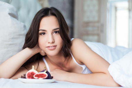 Attractive woman with a figs on the bed Stock Photo - 23235522