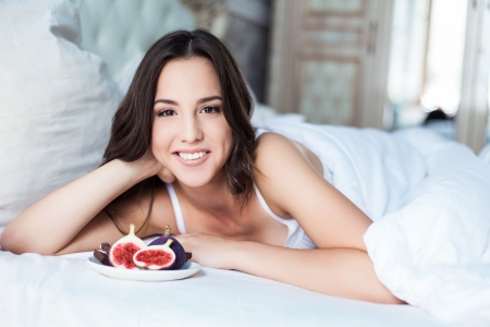 Attractive woman with a figs on the bed Stock Photo - 23235523