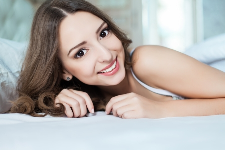 Portrait of young woman at the bed at early morning photo