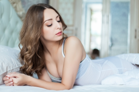 Portrait of young woman at the bed at early morning