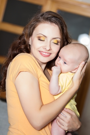 mother with her cute baby on the couch at home photo