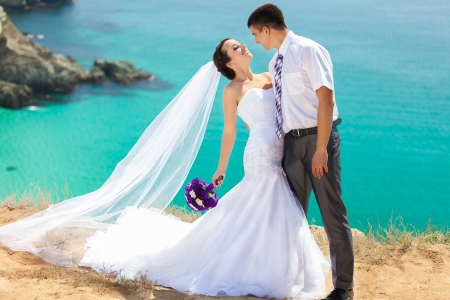 wedding couple stands on a cliff, blue sea on background photo