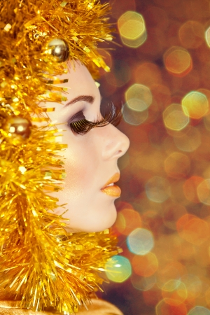 Christmas makeup of beautiful woman with gold tinsel on face photo