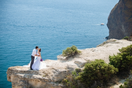 wedding couple stands on a cliff above blue sea photo