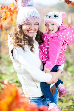 Young mother and her cute girl have fun in autumn vineyard photo