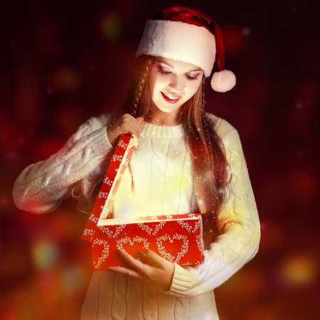christmas, new year concept - Surprised girl in Santa hat photo