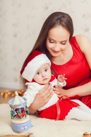 Portrait of happy mother and cute baby in suit of Santas little helper