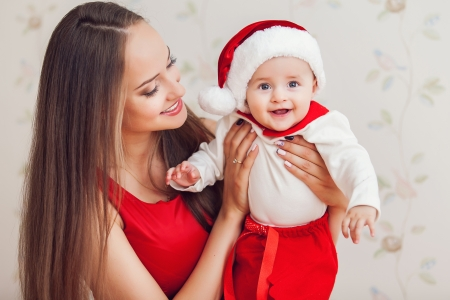 christmas baby: Portrait of happy mother and cute baby in suit of Santas little helper