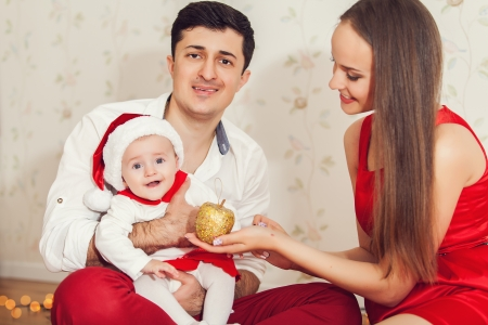 Portrait of happy family with cute baby in suit of Santas little helper photo