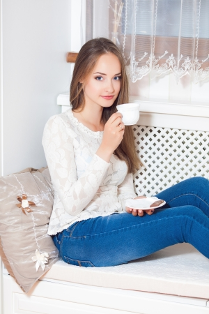 Happy young woman sitting, holding coffee mug, laughing Stock Photo - 24265167