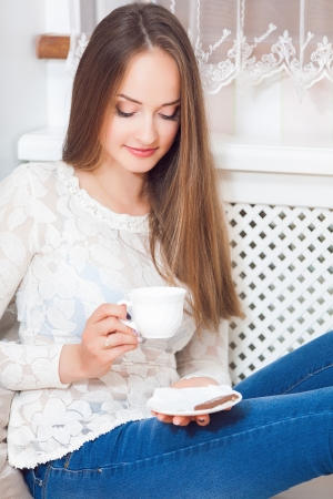 Happy young woman sitting, holding coffee mug, laughing Stock Photo - 24265177