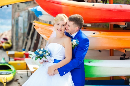wedding couple stand near colorful boats photo