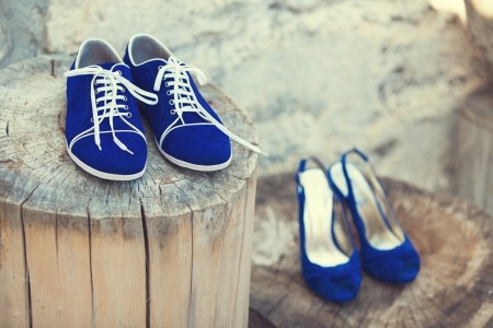 blue footwear of bride and groom on a wooden stump Stock Photo