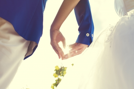newly wedded couple: wedding couple hands touching fingers in the shape of hearts. Bright light of the sun on . Stock Photo