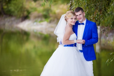 Happy newlyweds with beautiful lake behind