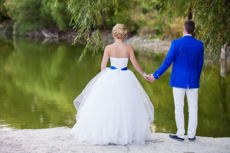Happy newlyweds with beautiful lake behind photo