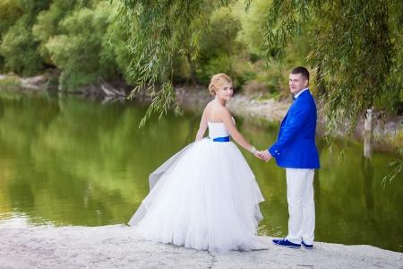 Happy newlyweds with beautiful lake behind photo