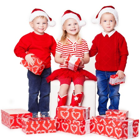 Group of three children in Christmas hat with presents over white  photo