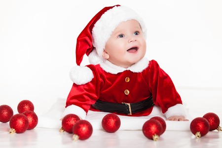 little santa baby with christmas hat lying over white background photo