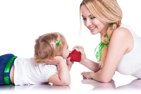 portrait of young mother and little daughter holding heart photo