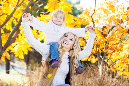Young mother playing with her daughter in autumn park photo