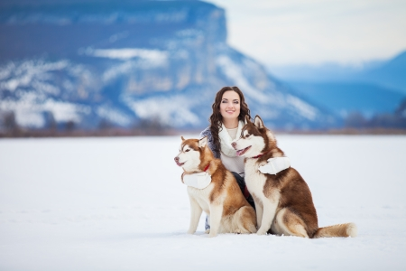 Happy young girl playing with siberian husky dogs in winter park. photo