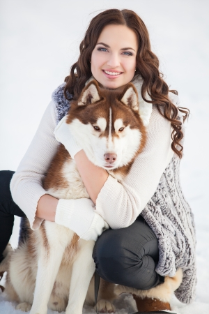 Girl embracing cute dog in winter park photo