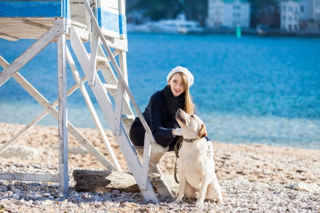 Beautiful young woman playing with dog on the sea shore photo