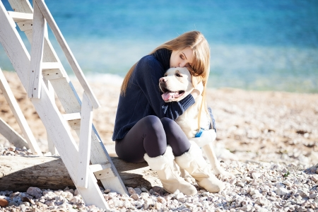 trusting: Beautiful young woman playing with dog on the sea shore
