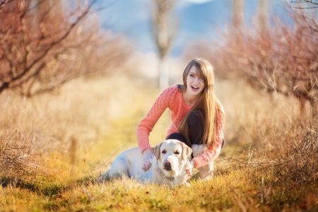 Portrait of beautiful young woman playing with dog at the park photo