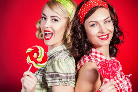 Beautiful pinup girls with lollipop on red background photo