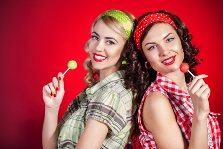 pretty girl: Beautiful pinup girls with lollipop on red background Stock Photo