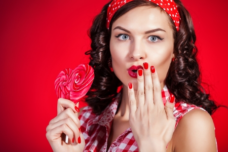 Young pin-up girl with lollipop on red background photo